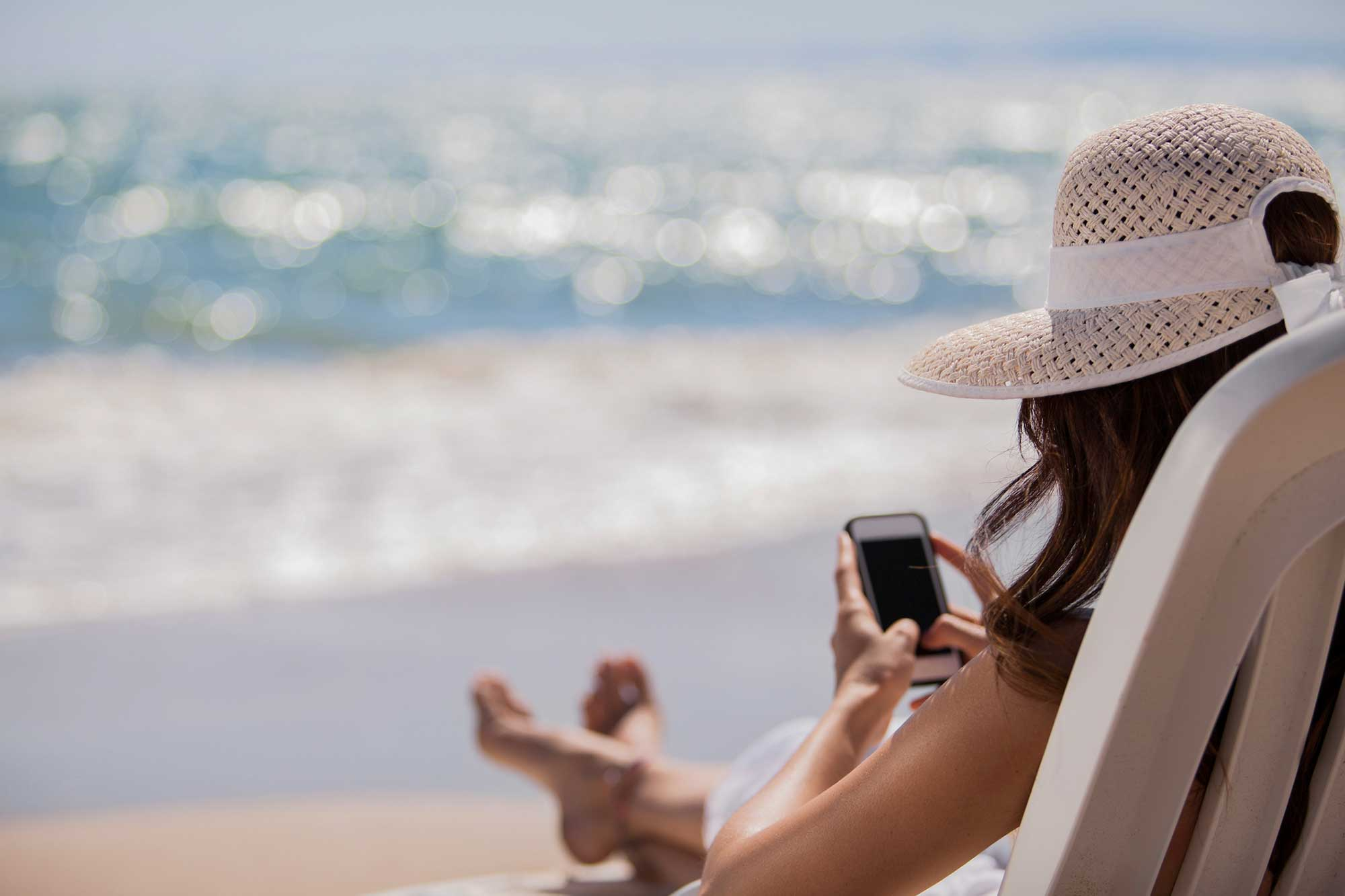 Woman on the beach looking at her cell phone