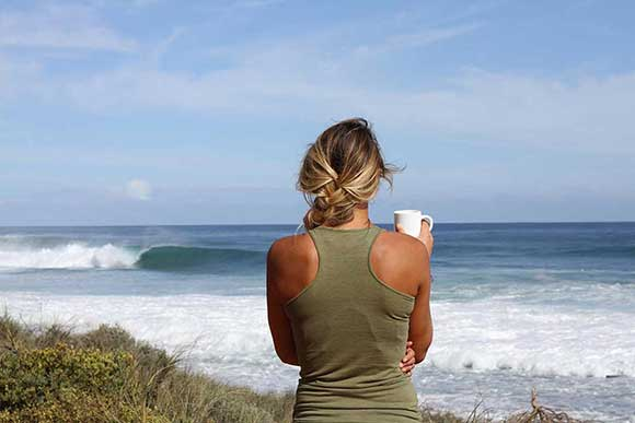 Woman lesisurely enjoying her coffee watching the ocean view