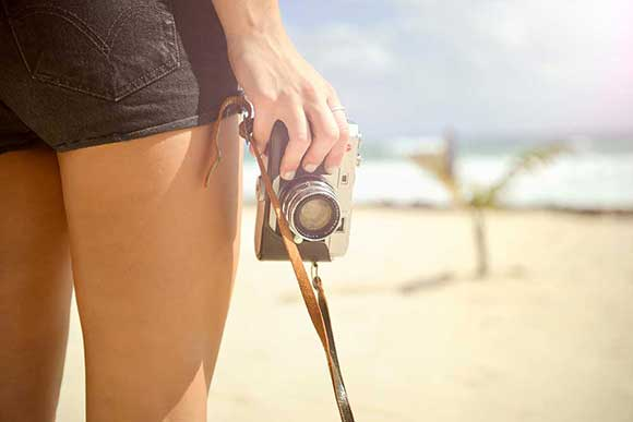 Women holding camera by the beach